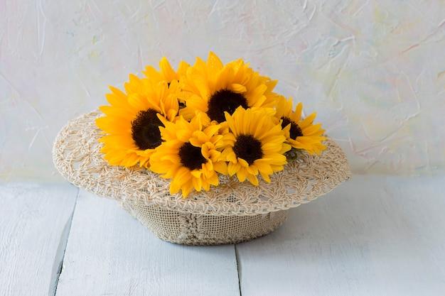 Bouquet de tournesols dans un chapeau de paille sur une table en bois blanche Photo Premium