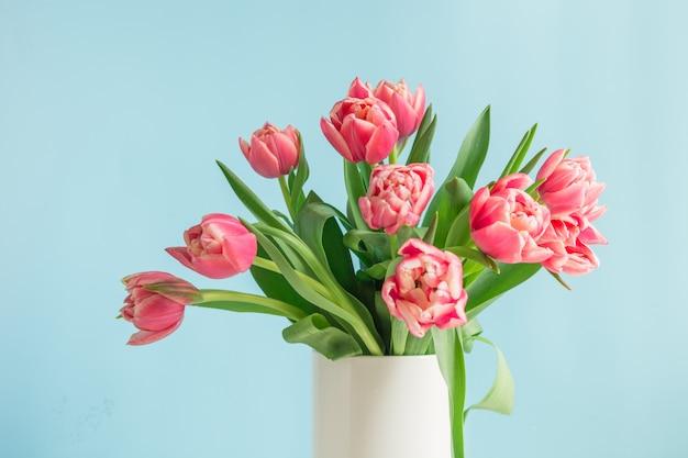 Bouquet De Tulipe Rouge Dans Un Vase Sur Bleu. Fête Des Mères. Photo Premium
