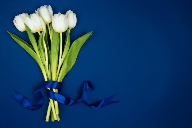 Un Bouquet De Tulipes Blanches Attachées Avec Un Ruban. Sur Fond Bleu. Carte Postale Pour La Saint Valentin Et Le 8 Mars Photo Premium
