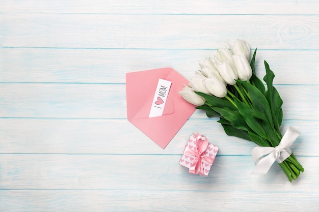 Un bouquet de tulipes blanches avec une boîte cadeau, une note d'amour et une enveloppe de couleur sur des planches en bois bleues. fête des mères Photo Premium