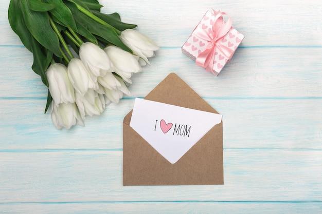 Un bouquet de tulipes blanches avec une boîte cadeau, une note d'amour et une enveloppe sur des planches en bois bleues. fête des mères Photo Premium