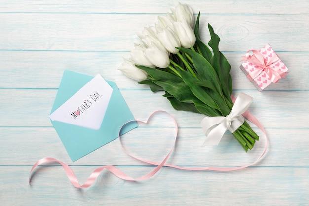 Un bouquet de tulipes blanches et un ruban rose en forme de cœur avec une boîte-cadeau, une note d'amour et une enveloppe de couleur sur des planches en bois bleues. fête des mères Photo Premium