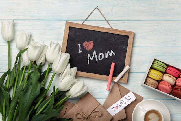 Un bouquet de tulipes blanches avec un tableau noir, une tasse de café, une note d'amour et des macarons sur des planches en bois bleues. fête des mères Photo Premium
