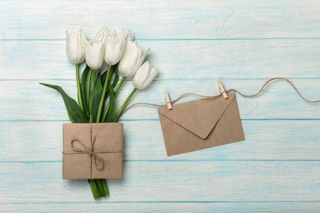 Un bouquet de tulipes blanches, une tasse de café avec une note d'amour et une enveloppe sur des planches en bois bleues. fête des mères Photo Premium