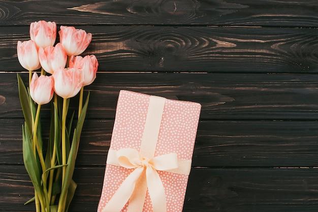 Bouquet de tulipes avec boîte-cadeau sur la table en bois Photo gratuit