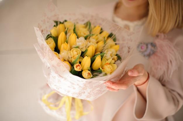Bouquet de tulipes jaunes dans les mains de la fille Photo Premium