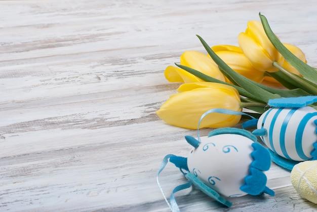 Bouquet de tulipes jaunes et oeufs de pâques chikken avec un ruban bleu sur un fond en bois Photo Premium