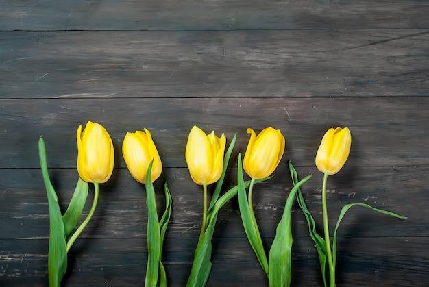 Bouquet de tulipes jaunes avec un ruban jaune sur un fond en bois Photo Premium