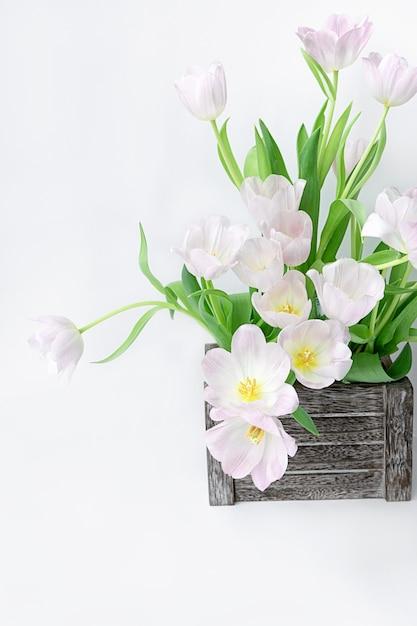 Un Bouquet De Tulipes Légèrement Roses Dans Une Boîte En Bois Sur Un Fond Blanc. Photo Premium