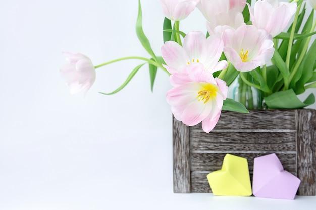 Un Bouquet De Tulipes Roses Dans Une Boîte En Bois Et Deux Coeurs En Papier De Couleur Jaune Et Lilas Sur Fond Blanc. Photo Premium