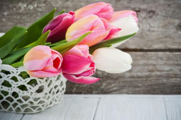 Bouquet de tulipes roses dans un panier au crochet Photo Premium
