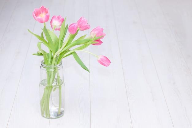 Bouquet De Tulipes Roses Dans Un Vase En Verre Sur Fond De Bois Blanc. Copiez L'espace. Fond De Printemps, Vacances, Concept D'anniversaire. Photo Premium