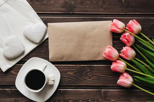 Bouquet de tulipes roses avec une tasse de café et de pain d'épice blanc en forme de coeur Photo Premium