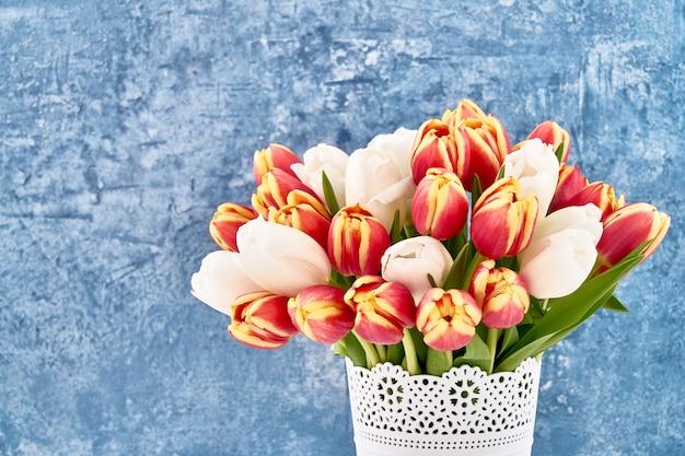 Bouquet de tulipes rouges et blanches en pot de fleurs blanches sur bleu vif. Photo Premium