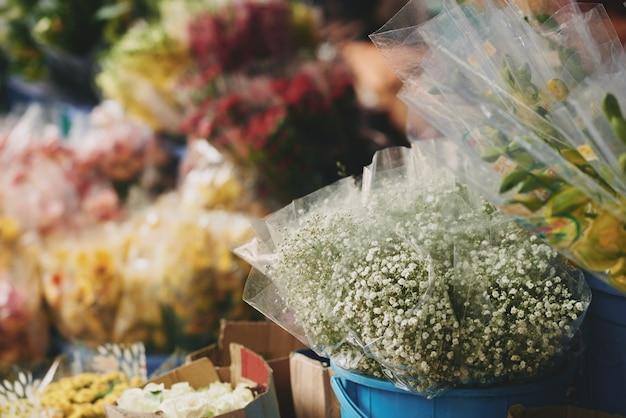 Bouquets de fleurs assorties présentées dans des seaux à l'extérieur du magasin de fleurs Photo gratuit