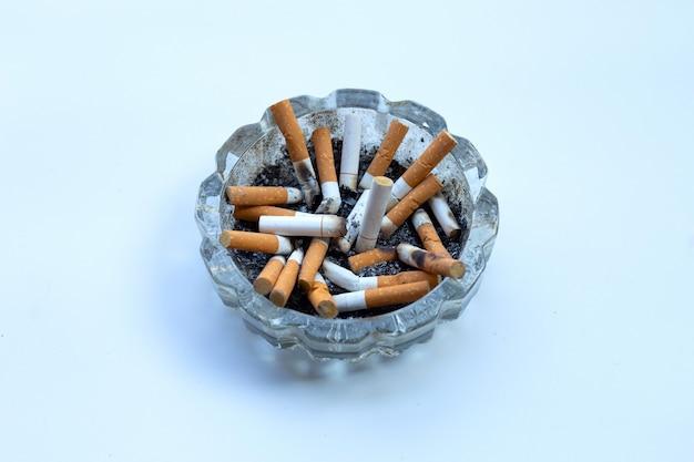 Bourgeons De Cigarettes Dans Un Cendrier Transparent Sur Blanc. Photo Premium