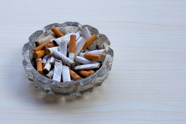 Bourgeons De Cigarettes Dans Un Cendrier Transparent Sur Table Photo Premium