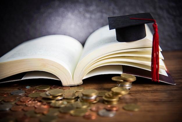 Bourses d'études pour le concept de l'éducation avec la pièce d'argent sur bois avec chapeau de graduation sur un livre ouvert Photo Premium