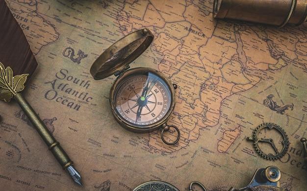 Boussole bronze antique avec couvercle sur la carte du vieux monde Photo Premium