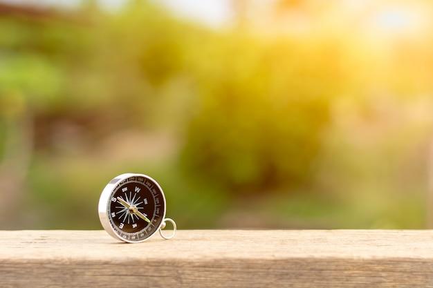 Boussole sur le bureau en bois dans la matinée. - pour concept voyageur Photo Premium
