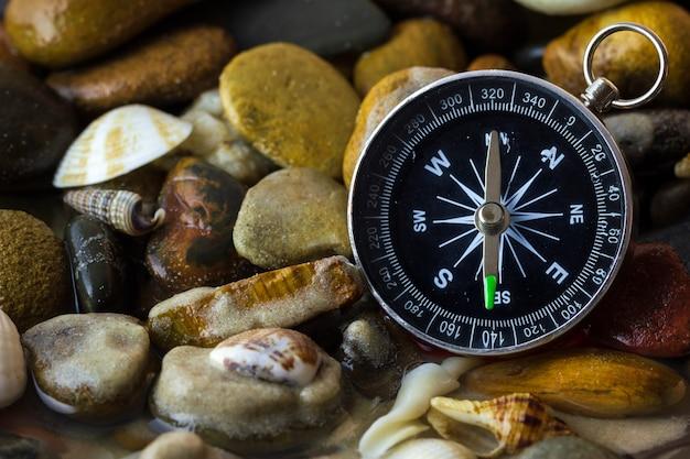 Boussole sur les galets et la coquille au bord de la rivière. notions de tourisme et d'aventure. Photo Premium