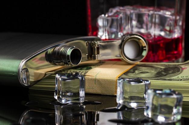 Bouteille en acier inoxydable alcool et glace sur table avec verre sur billet de dollar Photo Premium