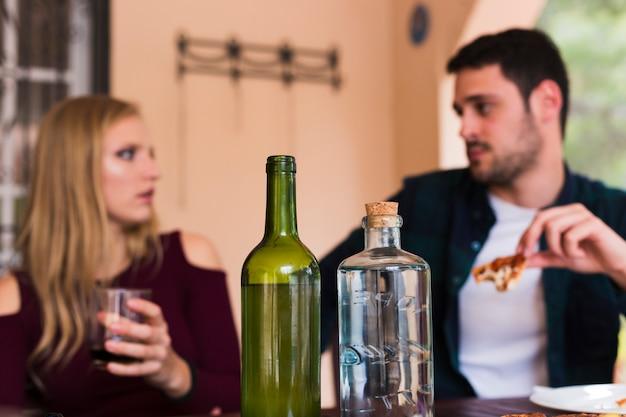 Bouteille d'alcool devant le couple qui mange de la nourriture Photo gratuit