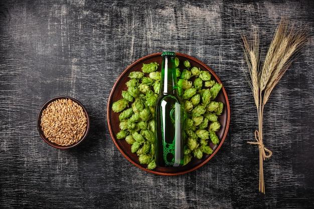 Une Bouteille De Bière Sur Un Green Hop Dans Une Assiette Avec Du Grain Et Des épillets De Blé Sur Le Fond Photo Premium