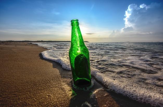 Bouteille de bière sur la plage Photo Premium