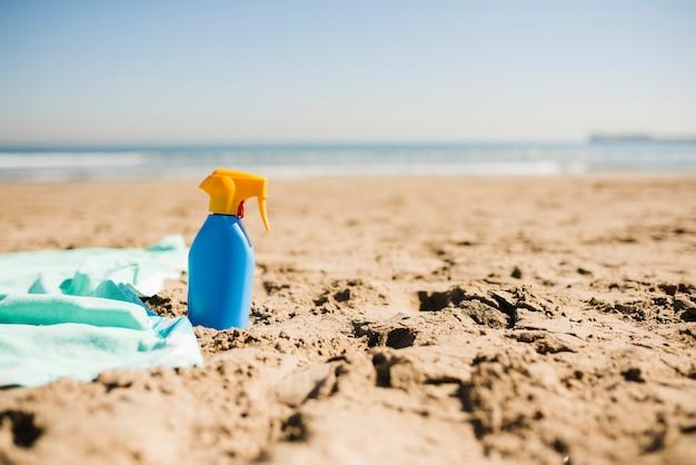 Bouteille bleue de lotion écran solaire sur la plage de sable fin Photo gratuit