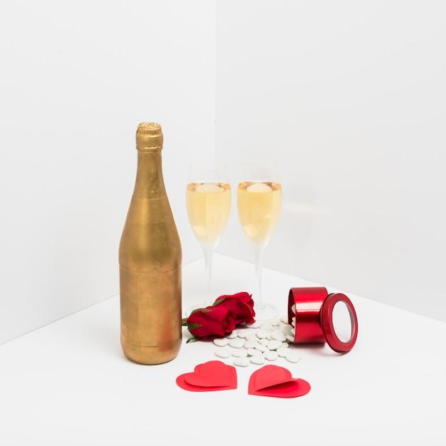 Bouteille de champagne avec des coeurs de papier Photo gratuit