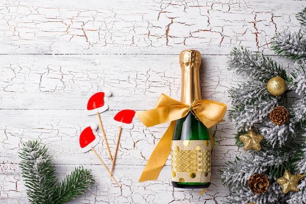 Bouteille de champagne dans un emballage d'or avec une décoration de noël Photo Premium