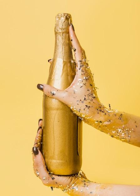 Bouteille De Champagne Dorée Tenue Dans Les Mains Photo gratuit