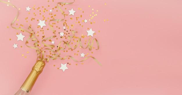 Bouteille De Champagne Avec Des étoiles De Confettis Et Des Banderoles De Fête Dorées Sur Fond Abstrait Rose. Concept De Nouvel An, Noël, Anniversaire Ou Mariage. Copyspace Vue De Dessus Horizontale Mise à Plat. Photo Premium