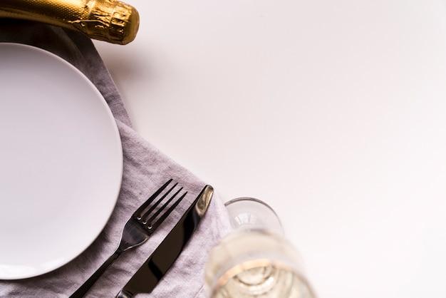 Bouteille de champagne et verre avec assiette vide sur fond blanc Photo gratuit