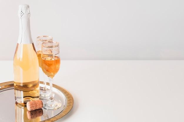 Bouteille Avec Des Coupes à Champagne Sur Un Plateau Photo gratuit