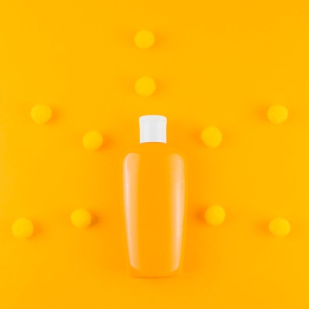 Bouteille de crème solaire avec pom pom de fil sur fond orange Photo gratuit