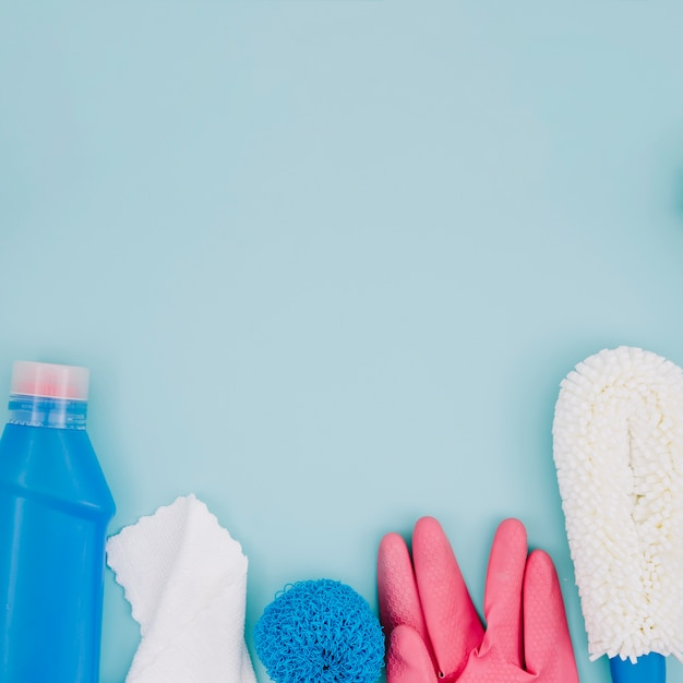 Bouteille de détergent bleu; serviette de table; éponge; gants roses sur fond bleu Photo gratuit