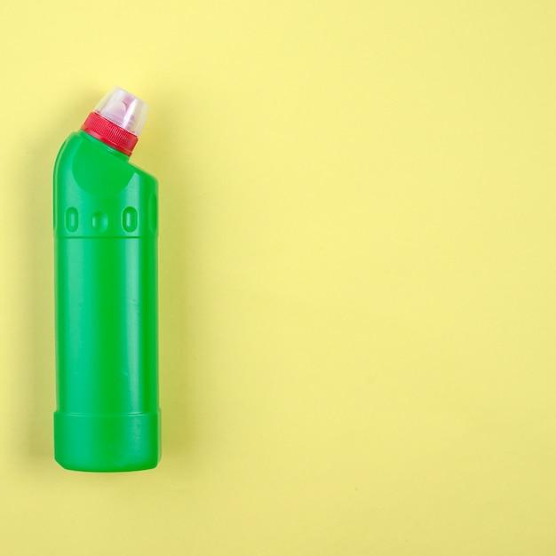 Bouteille de détergent en plastique vert sur fond jaune Photo gratuit