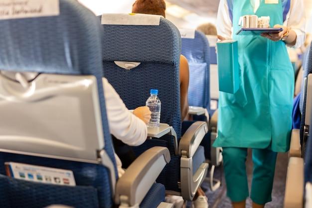 Une bouteille d'eau ciblée sélectionnée avec l'agent de bord sert de la boisson aux passagers à bord. Photo Premium