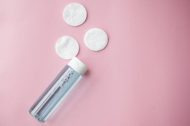 Bouteille avec eau nettoyante tonique ou micellaire et tampons de coton Photo Premium