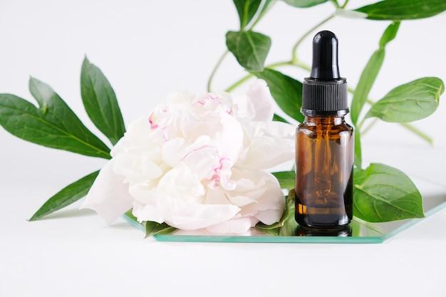 Bouteille D'huile Essentielle Aux Fleurs Blanches Photo Premium