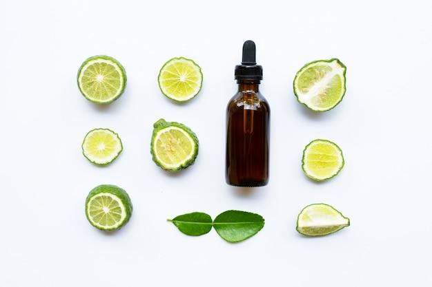 Bouteille d'huile essentielle et de citron vert kaffir frais ou de fruits de bergamote isolés sur blanc. Photo Premium