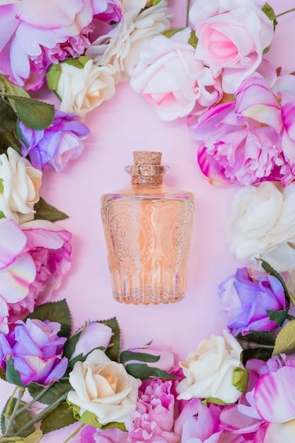 Bouteille d'huile essentielle entourée de fleurs fraîches sur fond rose Photo gratuit