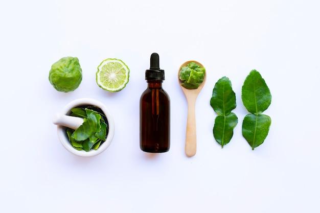 Bouteille d'huile essentielle et de limes de kaffir fraîches ou de fruits de bergamote avec des feuilles Photo Premium