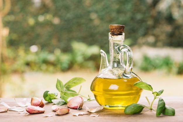 Bouteille d'huile d'olive brillante avec gralic à l'extérieur Photo gratuit