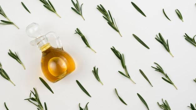 Bouteille d'huile d'olive avec des feuilles à côté de la table Photo gratuit