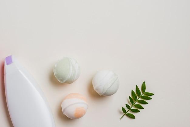 Bouteille hydratante; bombes de bain et feuilles sur fond blanc Photo gratuit