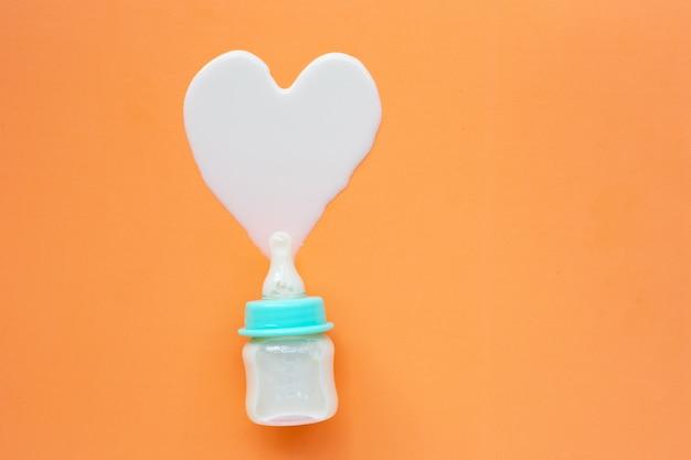 Bouteille de lait pour bébé sur orange Photo Premium