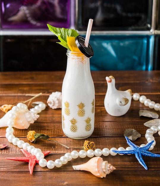 Bouteille de laiteux shake avec pipe et décors de plage. Photo gratuit